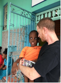 "<div class=""source"">courtesy of BARBARA LENGERS/Our Lady of Grace Catholic Church </div><div class=""image-desc"">Our Lady of Grace Catholic Church member Cameron Jackson interacts with one of the children at a Missionaries of the Poor center in Kingston, Jamaica.</div><div class=""buy-pic""></div>"